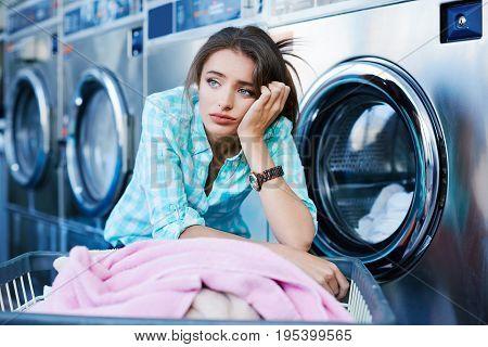 Bored Woman Near Washing Machines