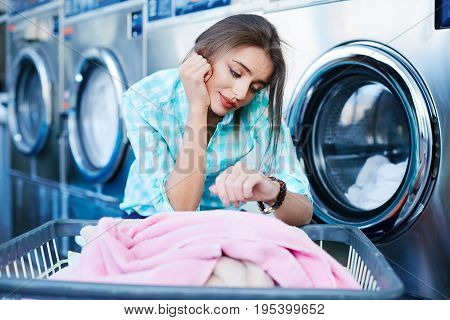 Woman Waiting Near Washing Machines