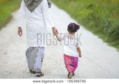 Mom Holding Her Baby Girl Hand With Hari Raya Dress