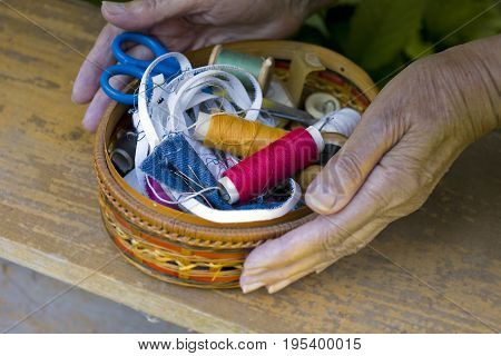 Female hands holding a wicker box with yarn needles and scissors
