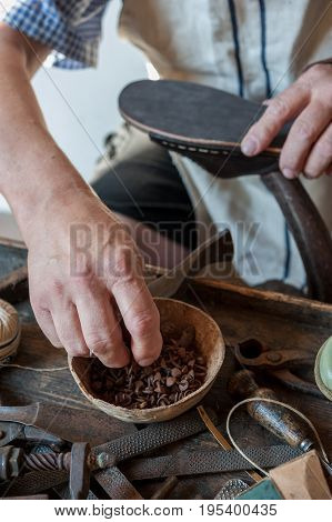 The shoemaker applies a bullet on the sole of a shoe. Various tools and instrument are placed on the work bench