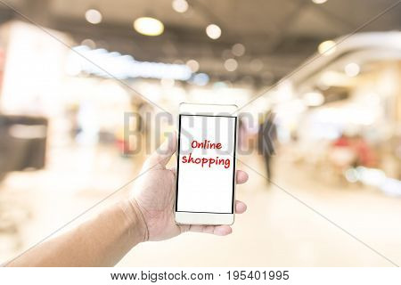 Hand holding smartphone and blurry shopping mall in background. Using smartphone to shopping concept.
