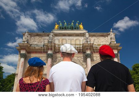 Paris France-June 17 2017: View on Arc de Triomphe in Paris and three young people with berets in the colors of the French flag.The Arc de Triomphe is one of the most famous monuments in Paris standing at the western end of the Champs Elysees at the cente