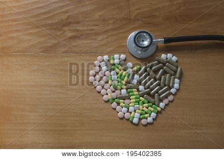 Drug pills in various shape and sizes on wooded table space for text Headphones doctor
