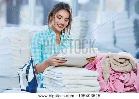 Woman Piling White Linen Into Heap