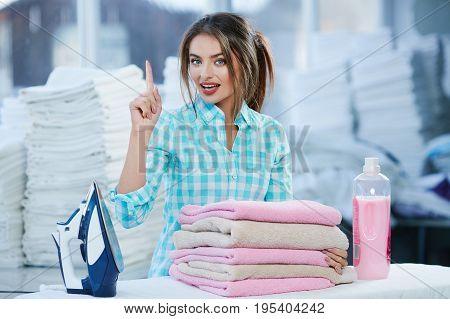 Girl Near Heap Of Rose Towels And Ironing Board