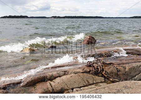 White foamy water waves hit into rocky seashore. Old rusty iron chain on rocks.