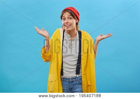 Nobody Cares About It. Young Pretty Female Wearing Yellow Anorak And Jean Overalls Shrugging Her Sho