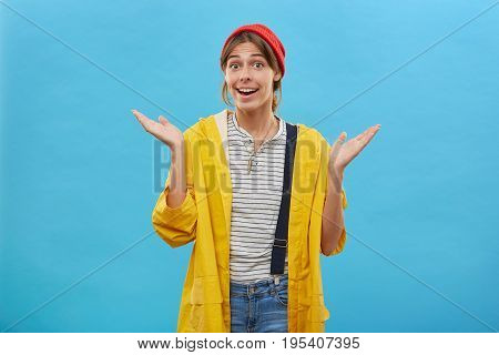 Beautiful Housewife Wearing Red Hat, Yellow Jacket And Jean Overalls Shrugging Her Hands, Raising Ey