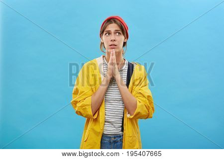 Religious Wife In Casual Wear Keeping Her Palms Together Praying For Wellness Of Her Husband Who Cam