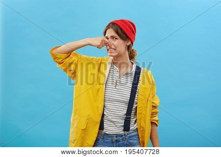 Young Female Keeping Hand On Nose Having Disgusting Look While Smelling Something Unpleasant Isolate
