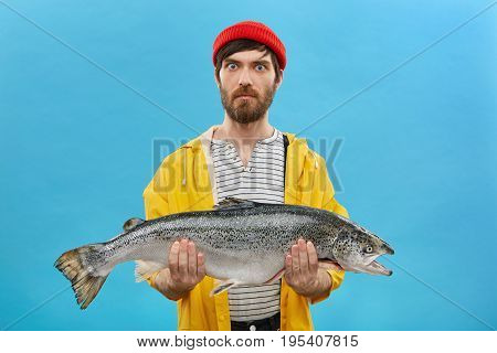 Indoor Shot Of Serious Surprised Fisherman With Blue Eyes And Beard Wearing Red Hat And Yellow Jacke
