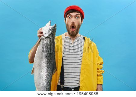 Astonished Bearded Fisherman Holding Heavy Fish Looking With Widely Opened Eyes And Mouth Being Very