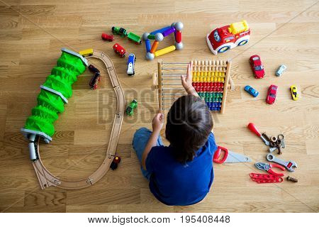 Preschool Child, Playing With Abacus And Other Toys, Sitting On Wooden Floor