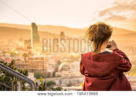 Girl taking photo of areal view at the sunset from high mountain of the TBILISI, GEORGIA