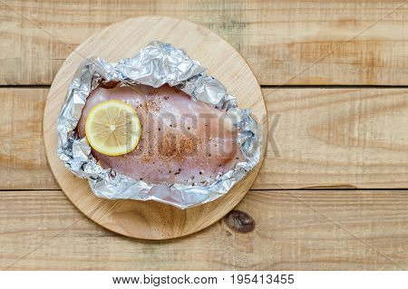 Background with raw chicken breast with lemon slice sea salt and black pepper in foil paper. Uncooked fillet on wooden board