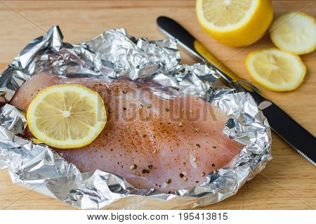 Raw chicken breast with lemon slice pepper seasoning and salt in baking foil