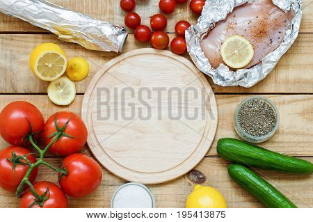 Background with round wooden board and variety of products. Raw chicken breast lemon tomatoes cucumber and seasoning