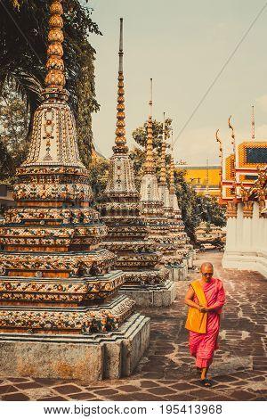 BANGKOKTHAILAND-MAY 172017: Thai monk is walking in front of old ancient pagoda at Wat Pho Temple in Bangkok Thailand.