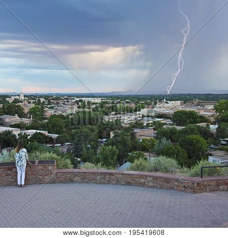 SANTA FE, NEW MEXICO, JULY 6. Fort Marcy Park on July 6, 2017, in Santa Fe, New Mexico. A Woman Watches a Lightning Storm from Fort Marcy Park in Santa Fe.