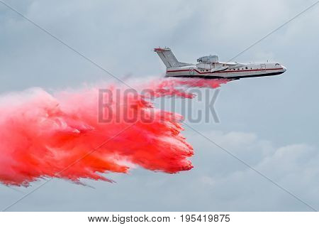 Firefighter Airplane Drops Red Water On A Fire In The Forest