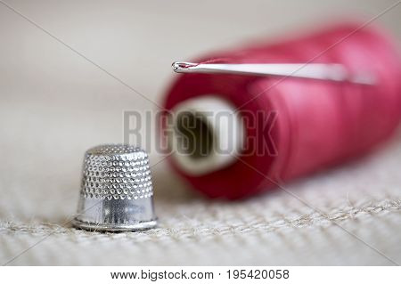 Hobby diy concept - old needle red thread and thimble