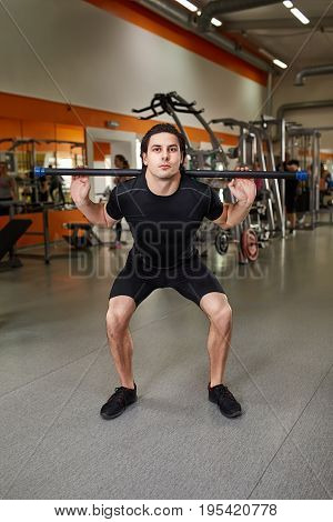 Young sporty man in the black sportwear with barbell doing squats in gym. Athlete man in the t-shirt, shorts and sporty shoes. Healthy lifestyle. Power and energy.