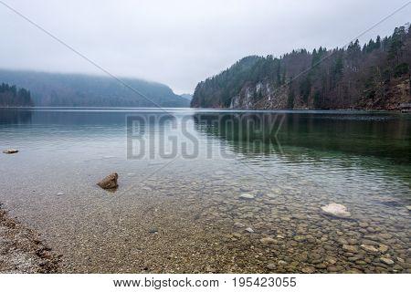 The Lake Alpsee On A Foggy Morning Near The Neuschwanstein Castle