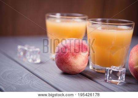 two glass with peach juice and two fresh peach fruits on grey background