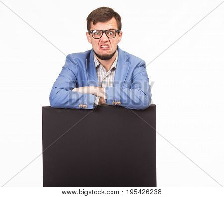 Young cross man portrait of a confident businessman showing presentation, pointing paper placard gray background. Ideal for banners, registration forms, presentation, landings, presenting concept.