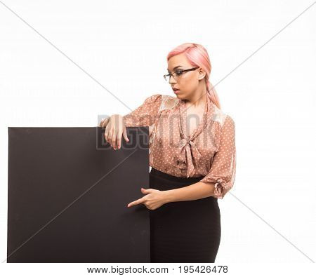 Young surprised woman portrait of a confident businesswoman showing presentation, pointing placard background. Ideal for banners, registration forms, presentation, landings, presenting concept.