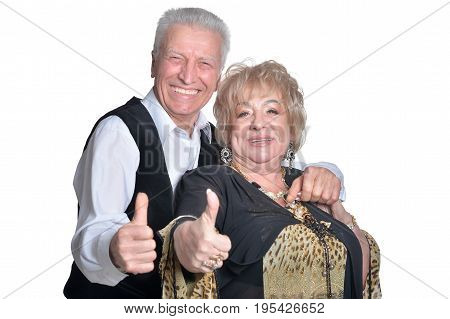 Senior couple smiling with thumbs up on white background