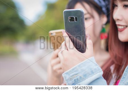 Women with friend are using a smartphone at Park.