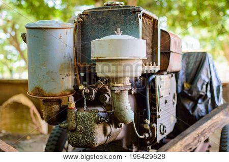 Old rusty motor engine of mobile electric generator on cart.