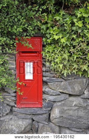 Victorian red post office mail box set into a stone wall.