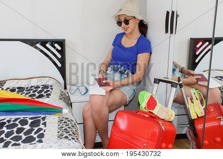 Happy young woman in colorful summer outfit sitting near the red staffed suitcase. Travel concept