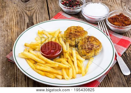 White plate with French fries and meat cutlets on wooden table. Studio Photo