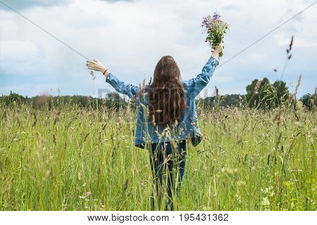 Happy Young girl with long hair standing with raised hands with beautiful summer bouquet of wildflowers in her hands. Concept of seasons, environment, natural beauty, summer hobbies, leisure and lifestyle on vacation