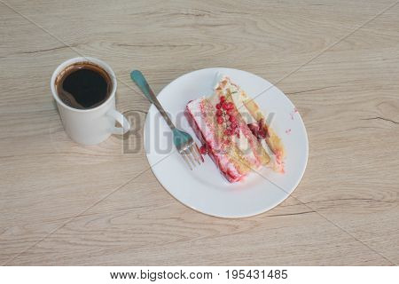 A cup of coffee and cake on wooden background. Fruit Cake with fresh red currant on the plate