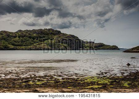 Assynt Peninsula Scotland - June 7 2012: Green rough hilly shoreline and flat trashy low-tide beach of Atlantic Ocean inlet near Kirkaig under heavy storm sky.