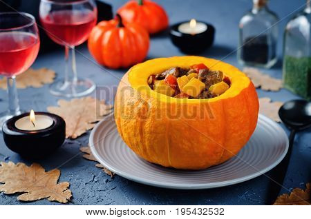 Pumpkin stuffed with meat and vegetables on a stone background