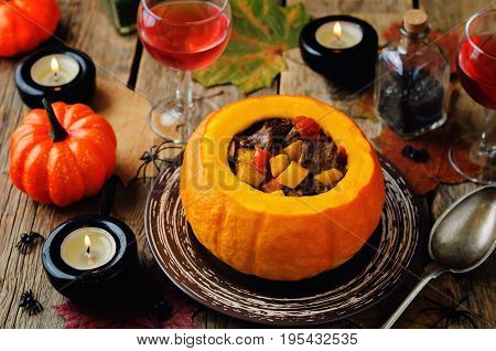 Pumpkin stuffed with meat and vegetables on a wood background