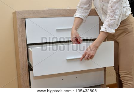 Woman Fixing A Drawer