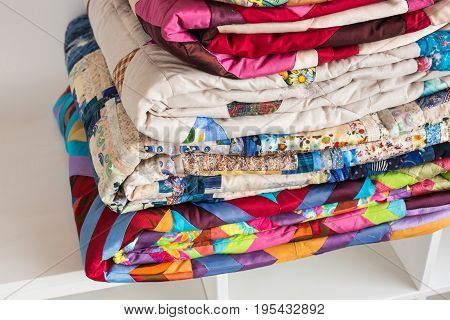 sewing, patchwork and fashion concept - macro of beautiful colorful quilts folded and stored in several rows in height for storage, sale of finished textile stitched products on white background