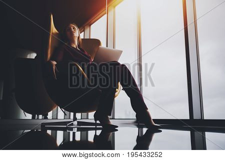 Charming tired lady sprawling out on elegant yellow armchair in luxury office after difficult work meeting beautiful caucasian businesswoman chilling after hard day and online conversation via laptop