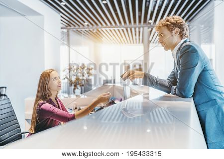 Handsome elegant caucasian man in formal suit is leaning on white table top of reception and giving his plastic card to beautiful female receptionist for payment bright office space or hotel around