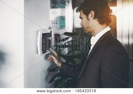 Handsome serious bearded employer in formal suit is adjusting lighting and air conditioning in office in the begging of work day using wall-mounted remote terminal with touch screen