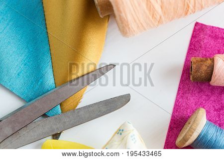 tailoring, sewing, patchwork and fashion concept - closeup tools on white work desk in studio, scissors, spools of blue and pink threads, meter, pieces of colored patchwork fabric, flat lay