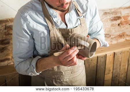 potter, workshop, ceramics art concept - closeup on young male's hands holding the clay cup and tools, a brunette ceramist with raw product at workplace, craftsman dressed in an apron