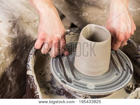 pottery, workshop, ceramics art concept - closeup on man's hands cuting off with string cutter semi-finished utensils product from top surface of Potter's wheel, unbaked clay cup, front view